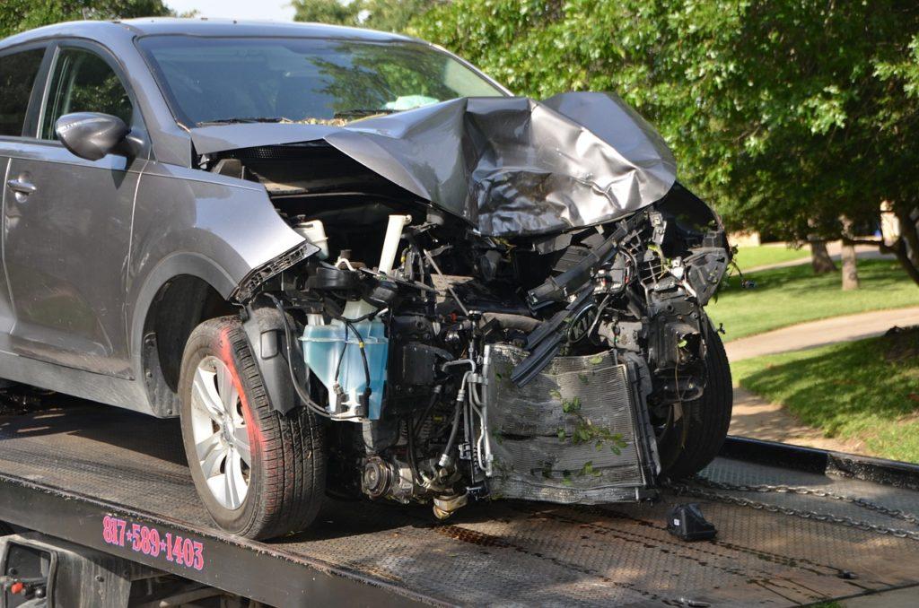 carro sendo rebocado com a frente destruída após uma batida