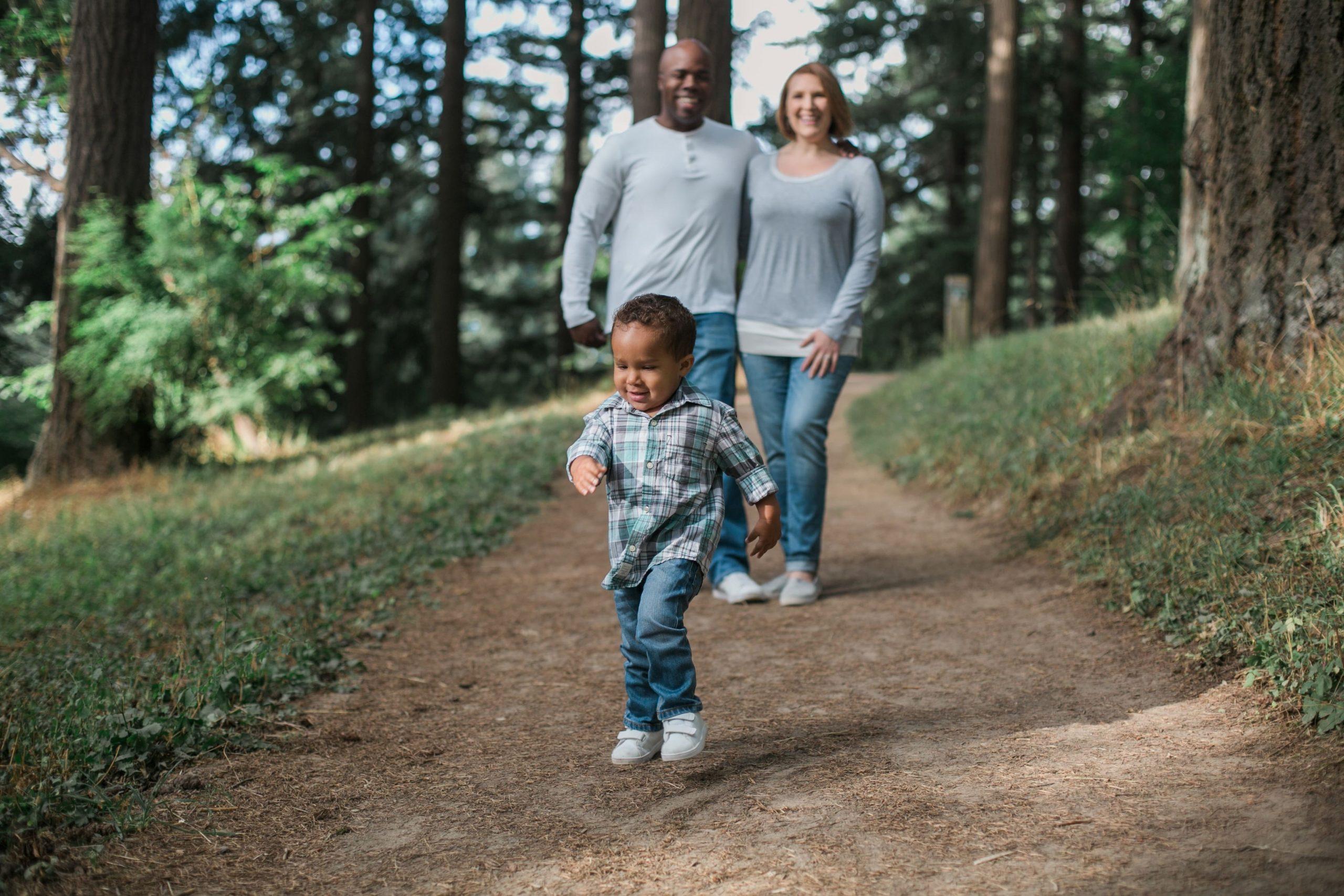 imagem de uma família feliz caminhando em uma trilha um homem uma mulher e uma criança pequena de dois anos todos estão sorrindo ilustrativo texto seguro de vida