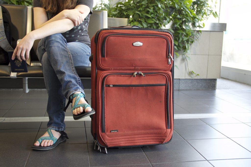 pessoa sentada no aeroporto com uma mala de viagem grande vermelha ao lado