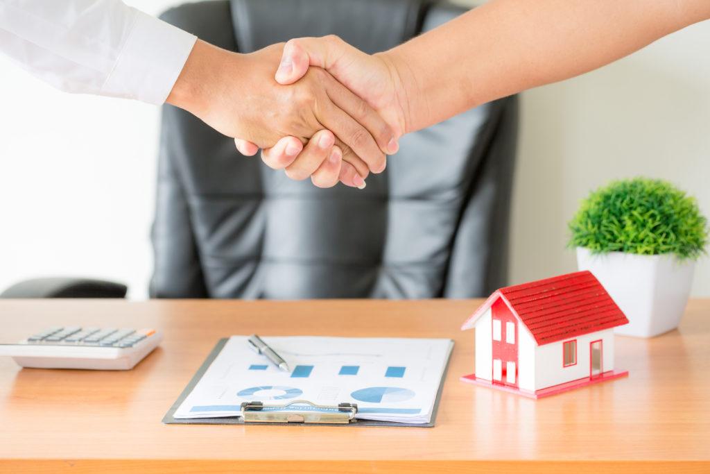 Vista lateral das mãos do agente e do cliente apertando as mãos após a assinatura do contrato. Em cima da mesa há uma maquete de uma casa, uma calculadora clara e um contrato.
