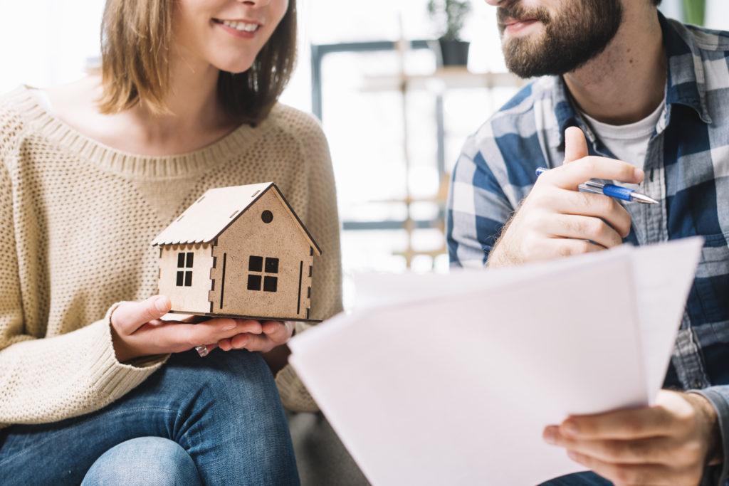 Uma mulher de blusa bege e calça jeans segurando uma casa em miniatura, sentada ao lado de um homem de blusa xadrez azul, segurando uma caneta e alguns papéis. Imagem ilustrativa para o texto franquia de plano de saúde.