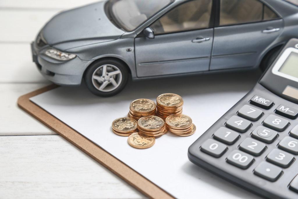 Em uma mesa branca encontra-se um modelo de carro, moedas e uma calculadora imagem ilustrativa texto franquia de seguro