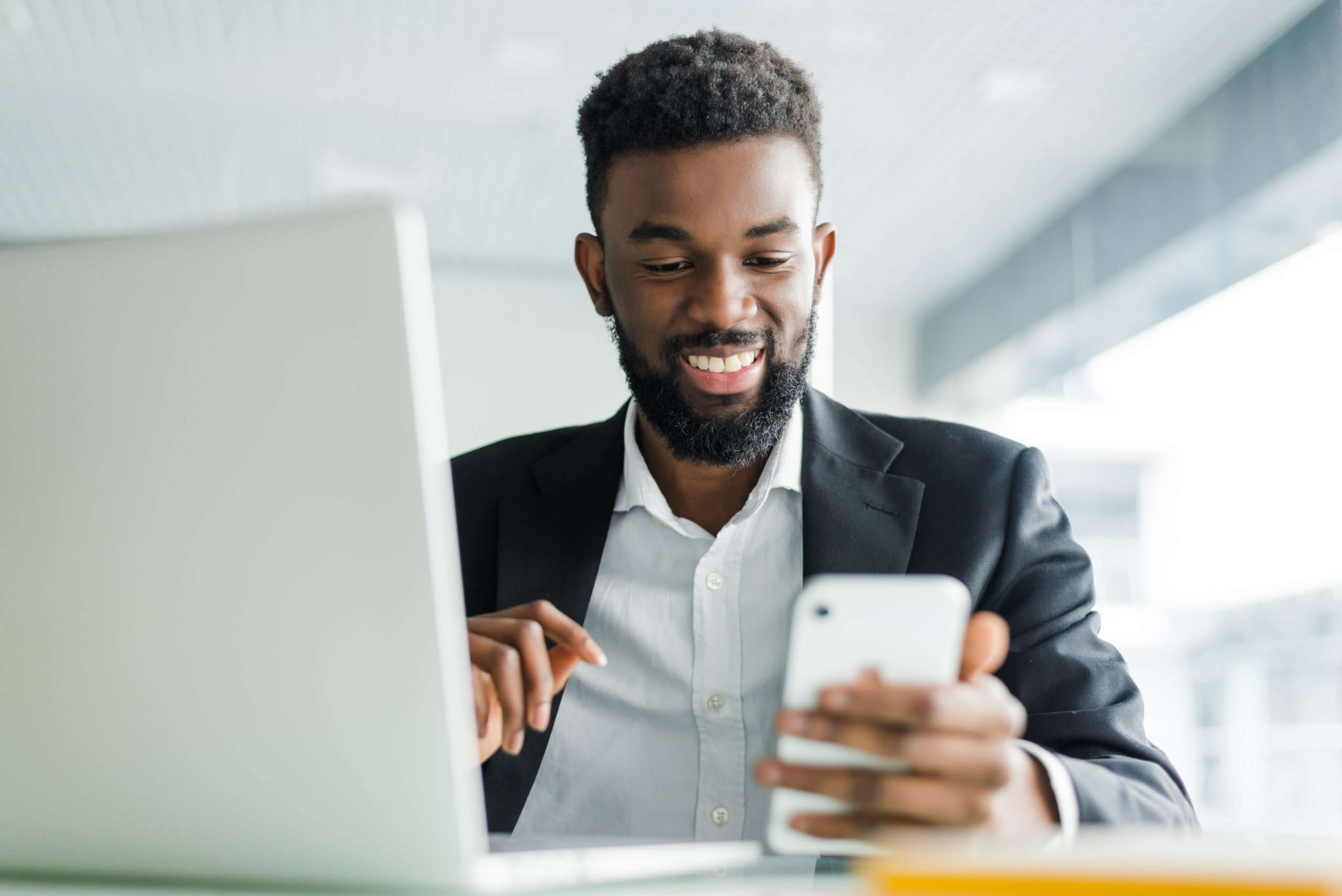 homem negro sorrindo sentado na cadeira em frente a um notebook e trabalhando olhando o celular imagem ilustrativa texto franquia de seguro