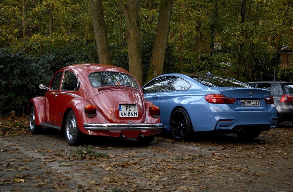 Foto de um fusca vermelho visto por trás, ao lado de uma BMW azul, também vista por trás. Ao fundo temos algumas árvores e plantas. Imagem ilustrativa para texto seguro de carro usado.