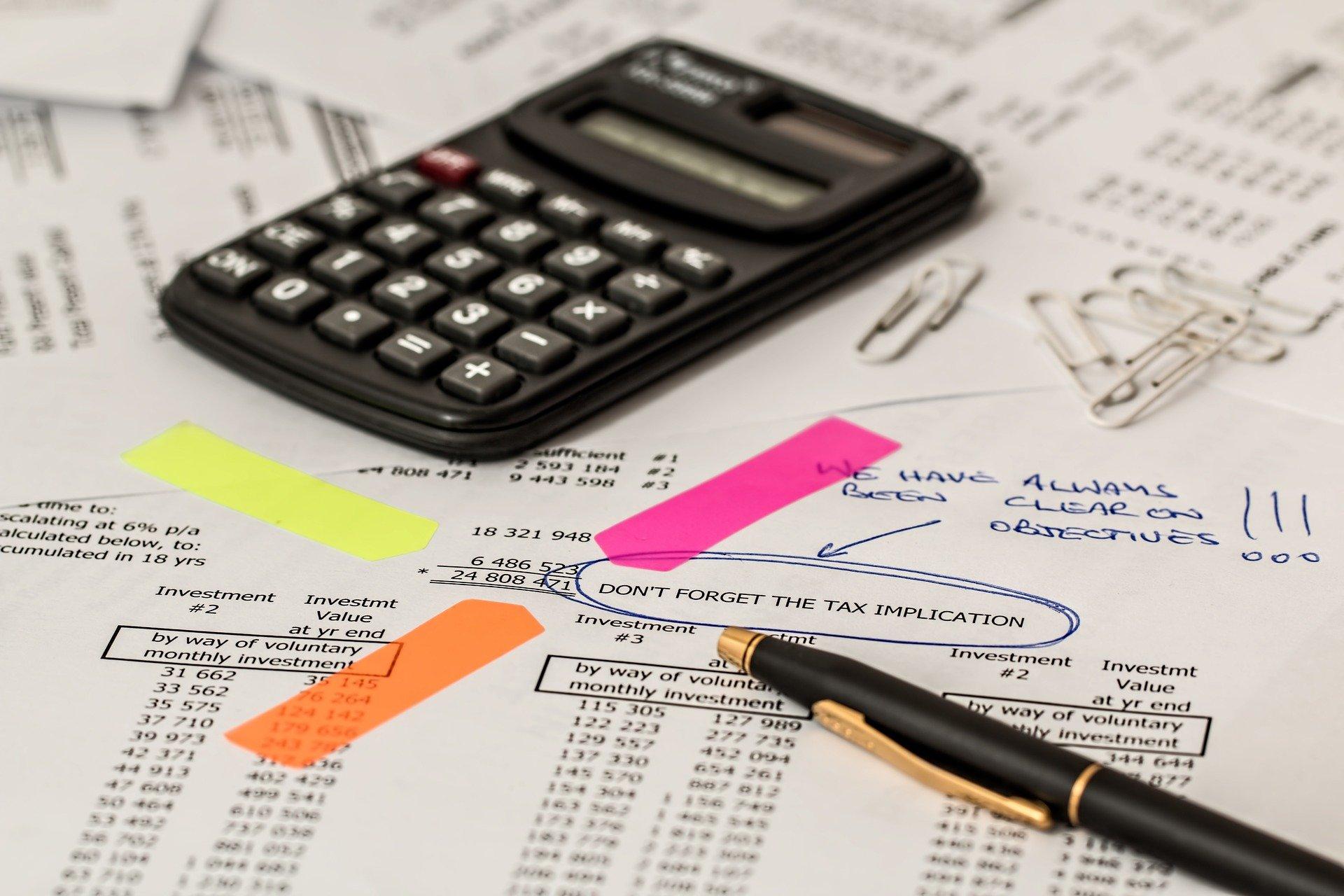 Imagem de uma calculadora preta, caneta preta e marcadores de papel laranja, amarelo e rosa, em cima de algumas folhas brancas com informações de contratos. Imagem ilustrativa para o texto apólice de seguro.