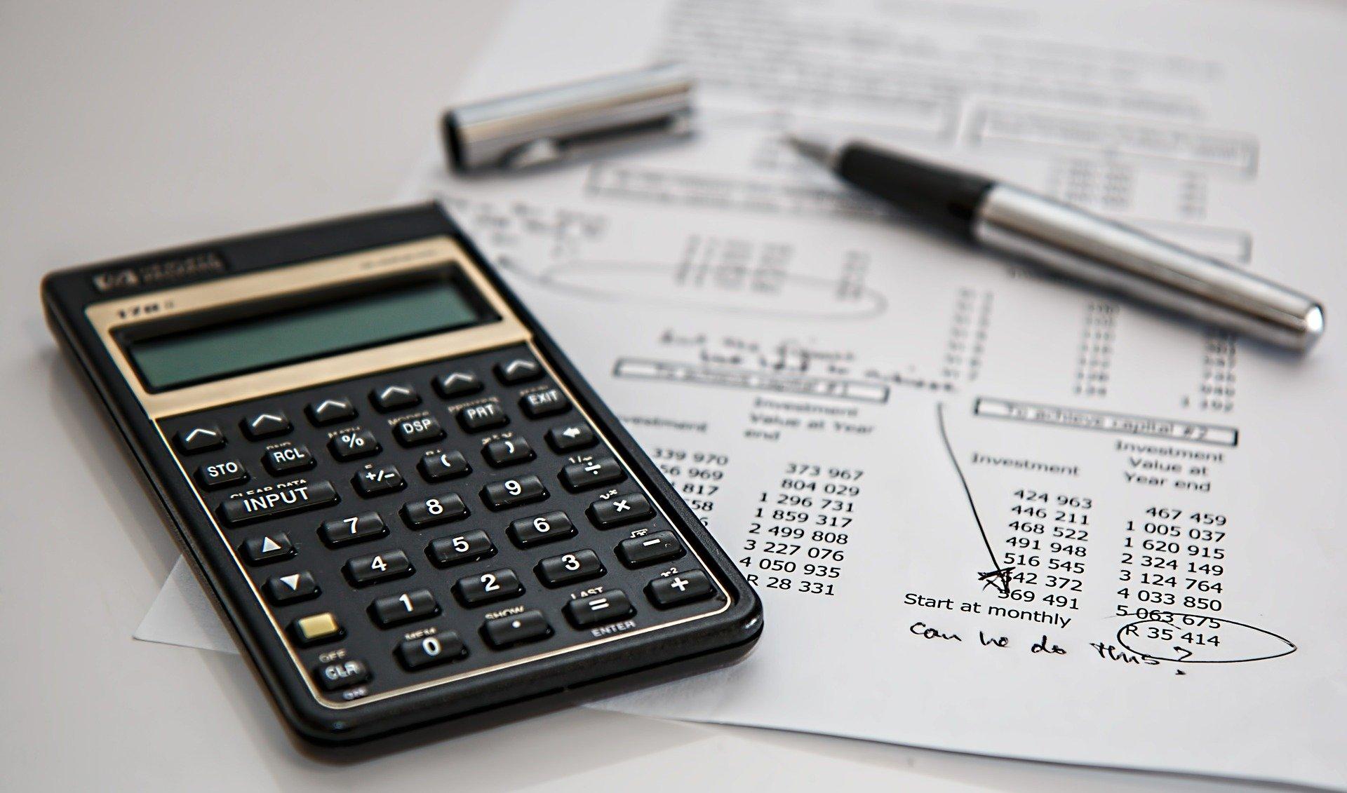 Imagem de calculadora preta e papeis e uma mesa branca com uma caneta. Imagem ilustrativa para o texto seguro de consórcio.
