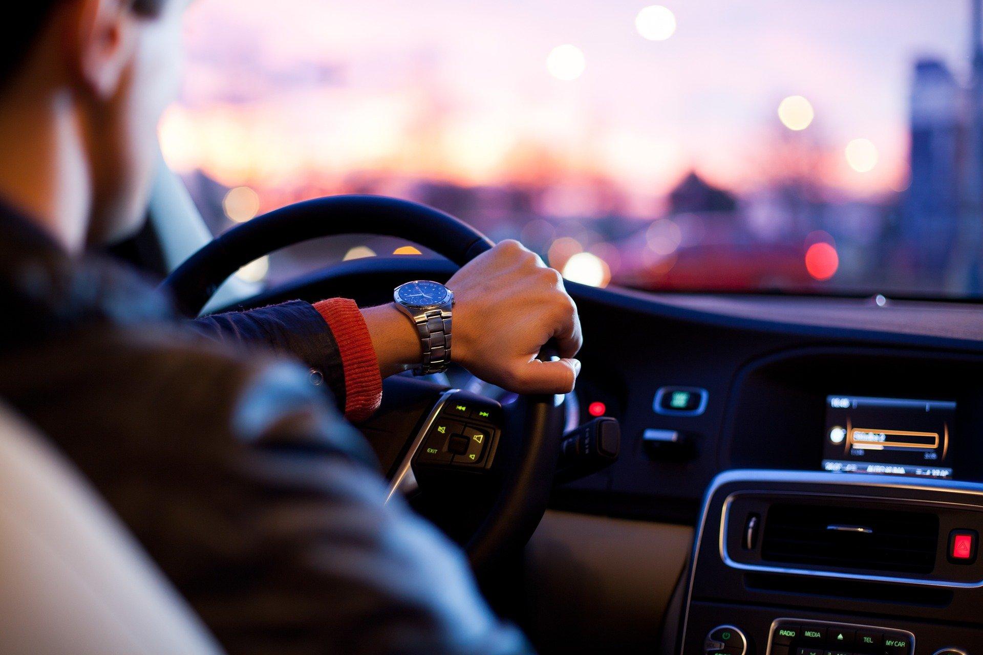Foto de um homem dirigindo um carro, todos os detalhes internos são pretos com algumas luzes. Pelo vidros temos uma paisagem desfocada em tom rosa e roxo. Imagem ilustrativa para texto proteção veicular.