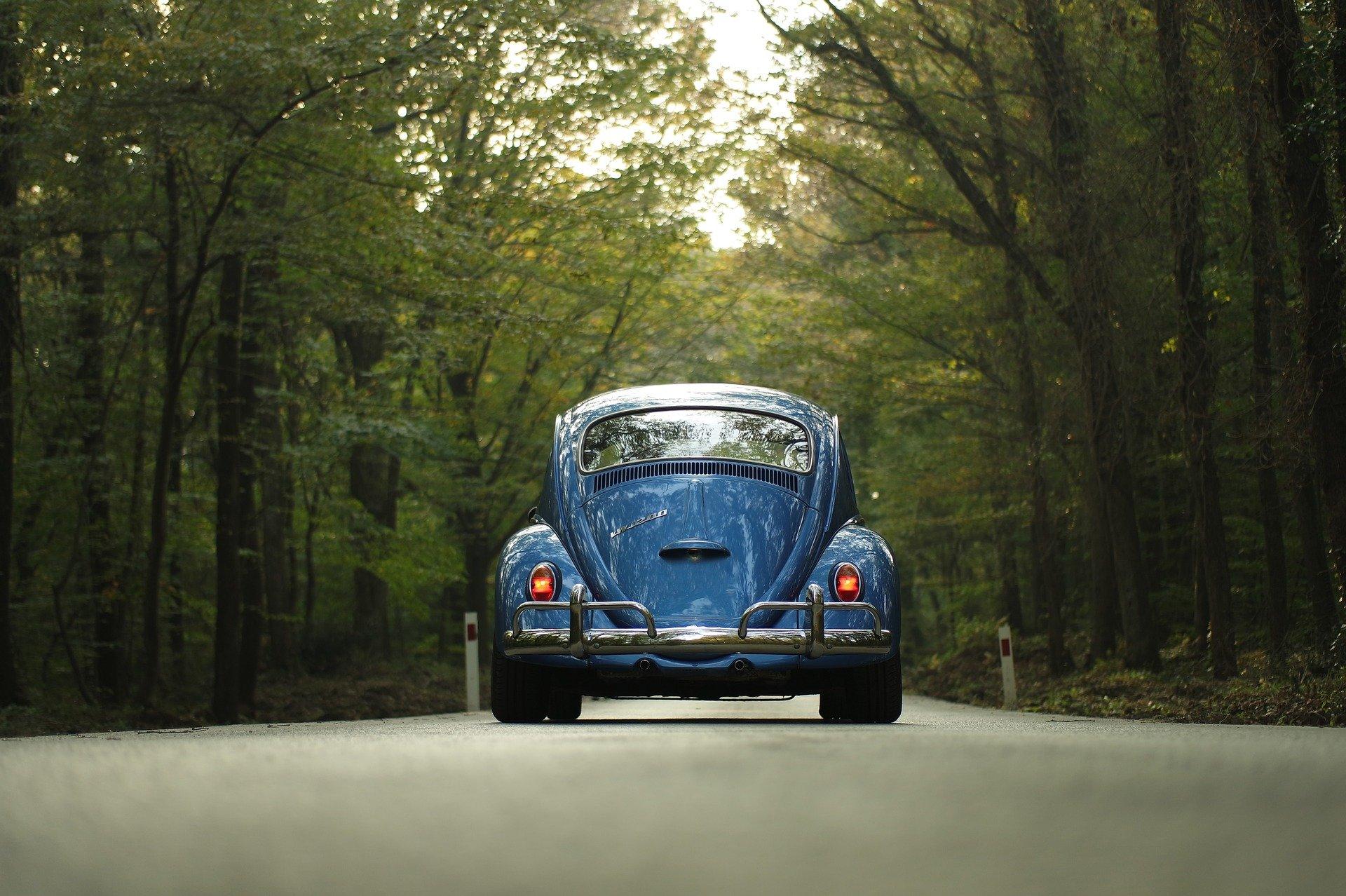 Foto de um fusca azul no meio de uma estrada asfaltada com muitas árvores ao redor. Imagem ilustrativa para texto franquia de seguro de carro.