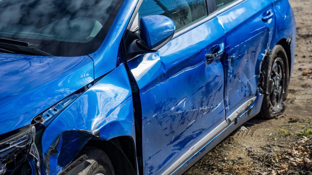 Foto de um carro azul com a lateral toda amassada. Imagem ilustrativa para texto seguro de carro novo.