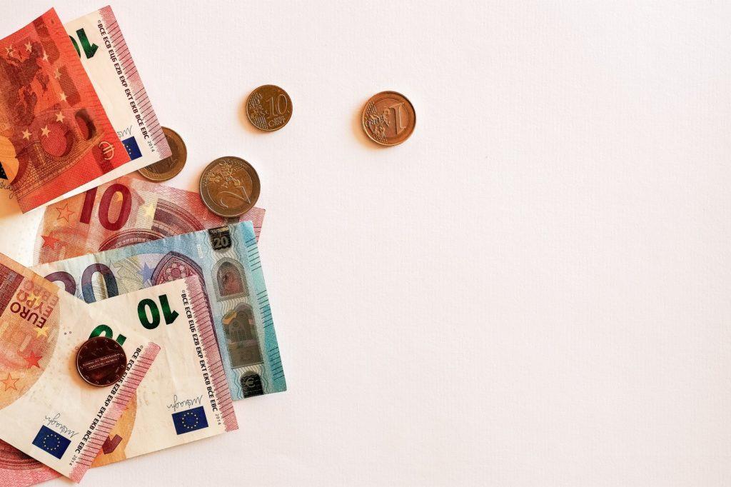 Foto de algumas notas de dinheiro e moedas espalhadas no canto esquerdo de um fundo bege.