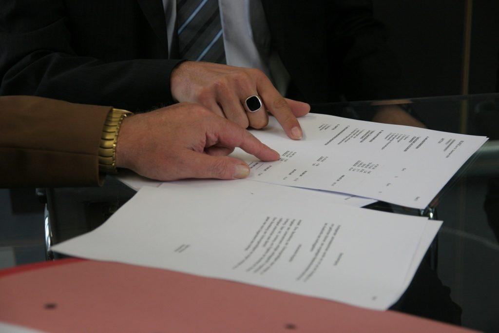 Duas mãos, de pessoas diferentes com roupas sociais apontando para informações em papéis que estão sobre uma mesa de vidro. Imagem ilustrativa para o texto apólice de seguro.