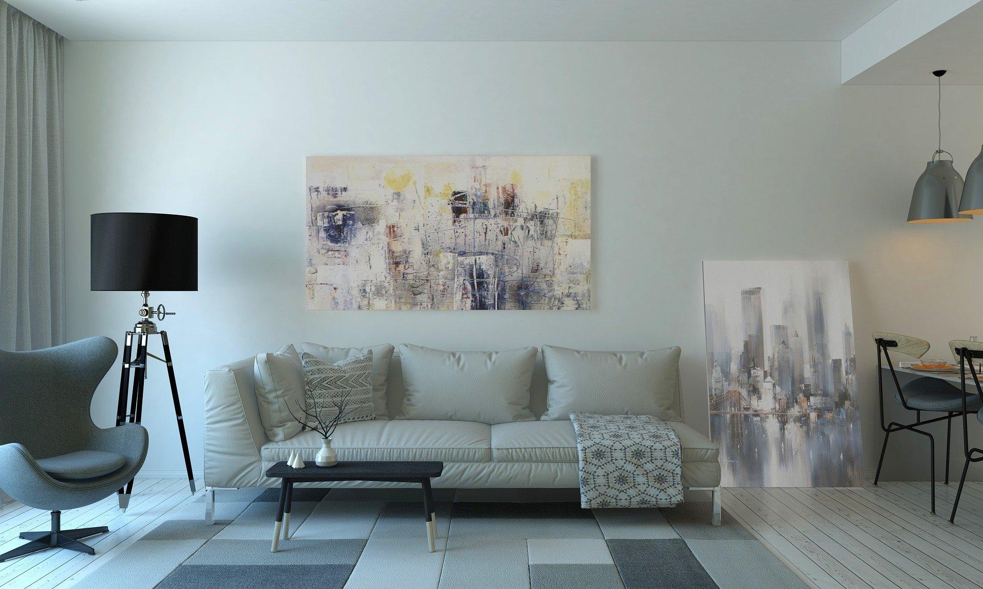 Foto de uma sala de estar com um sofá cinza no meio, uma poltrona azul no lado esquerdo, enquanto no chão temos um tapete com quadrados cinza e azul. Na parede ao fundo temos dois quadros com pintura abstrata e um abajur preto. No lado direito temos cadeiras pretas e um abajur cinza. Foto ilustrativa para texto vistoria seguro residencial.