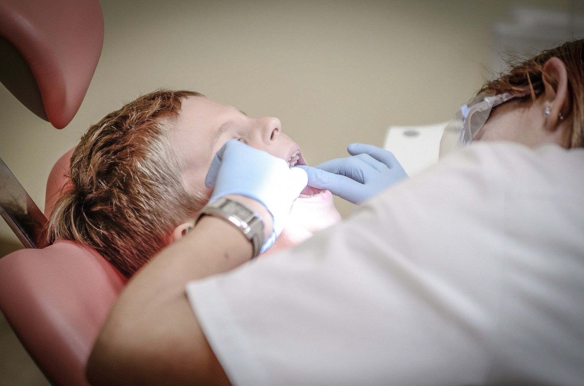 Imagem de uma criança enquanto recebe tratamentos odontológicos. O dentista usa roupa branca e luvas azuis. Imagem ilustrativa para o texto franquia de plano odontológico.