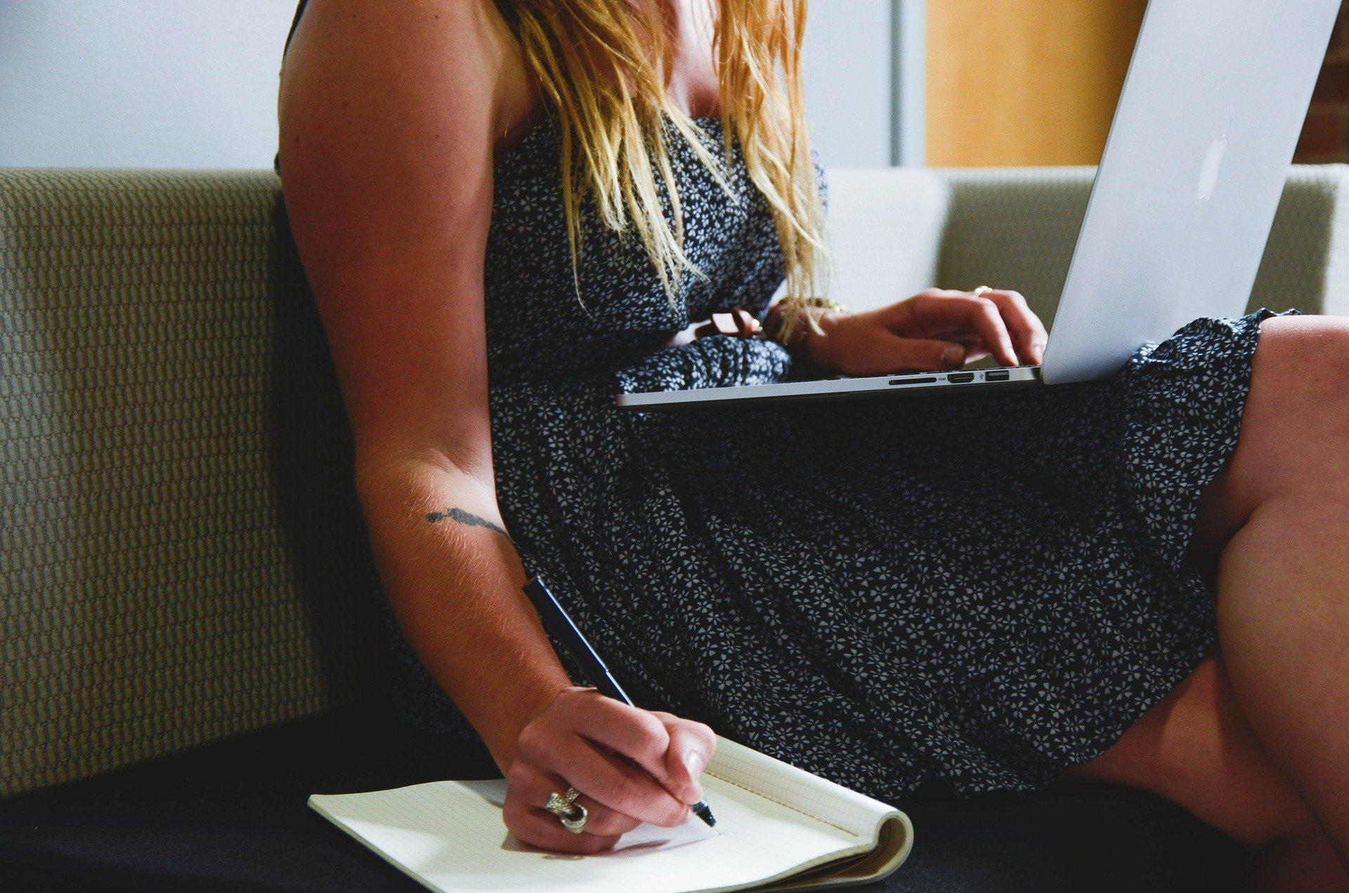 Foto de uma moça de vestido florido, sentada em uma sofá, segurando um notebook cinza enquanto usa a mão direita para escrever em um caderno com uma caneta preta.