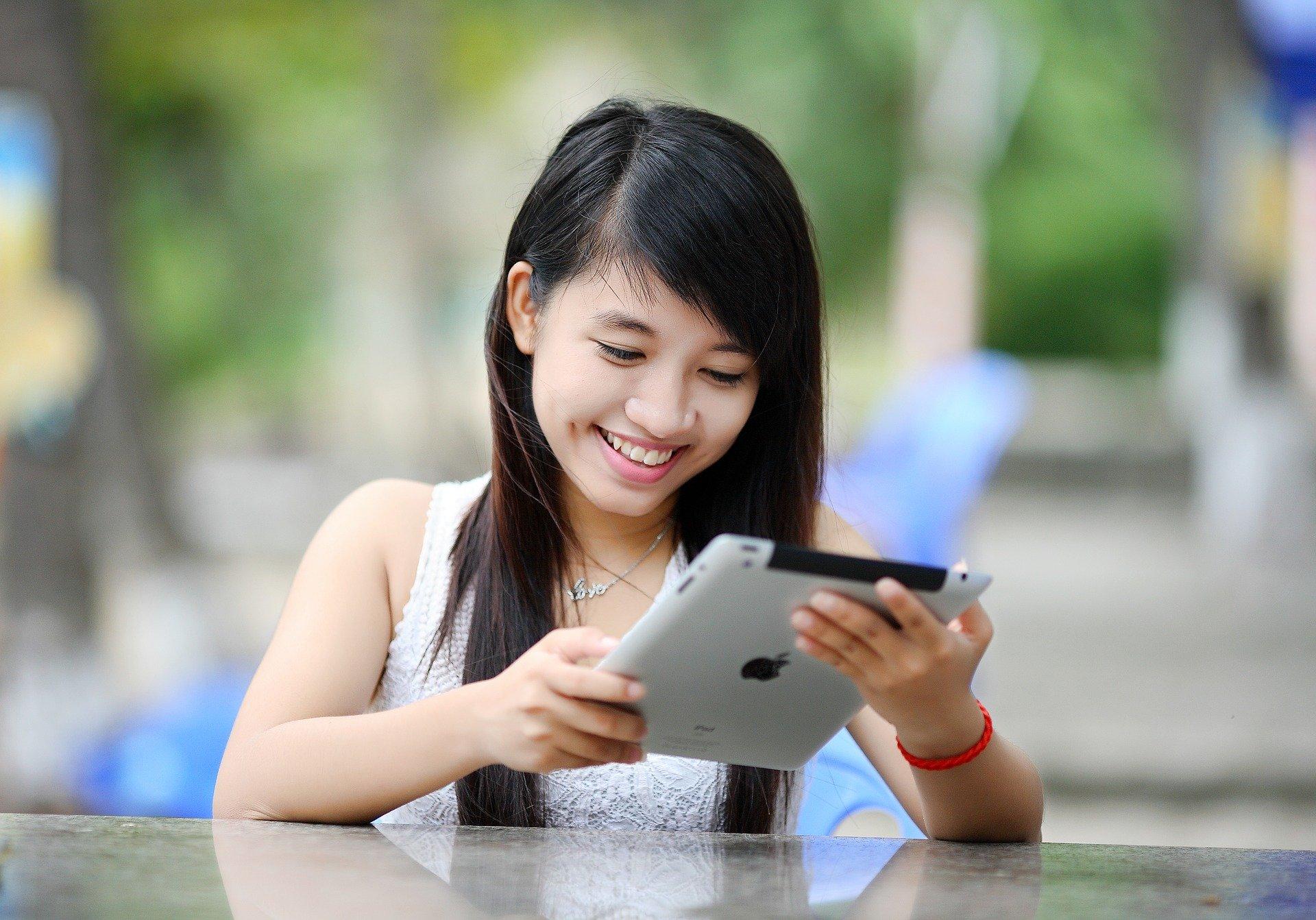 Foto de uma moça de camiseta branca apoiada em uma mesa branca enquanto segura um tablet. Temos também um fundo desfocado, mas é possível perceber árvores, como em um parque. Imagem ilustrativa para texto seguro.