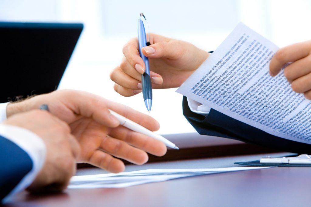Imagem focada nas mãos de duas pessoas com roupas formais, segurando papéis e caneta em cima de uma mesa escura. Imagem ilustrativa para o texto seguro de consórcio.
