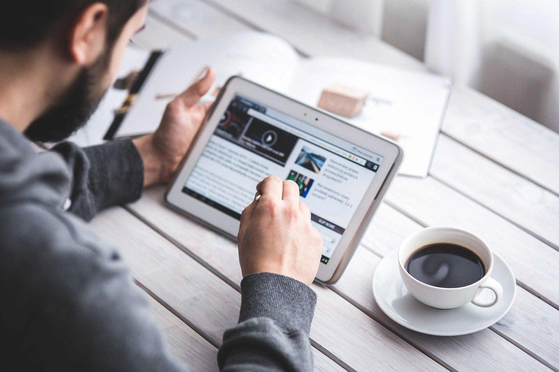 Foto de um homem com blusa social cinza de manga segurando um tablet com a mão esquerda, e utilizando a mão direita para mexer com uma caneta. Ao fundo temos uma mesa da madeira branca, com um livro aberto e uma xícara de café. Imagem ilustrativa para texto franquia de seguradora.