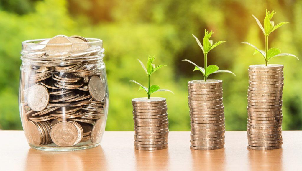 Imagem de um pote transparente com moedas e três colunas de moedas ao lado com plantas em cima de cada uma. Todos estão em uma mesa de madeira e ao fundo vemos um fundo verde com plantas. Imagem ilustrativa para o texto seguro de consórcio.