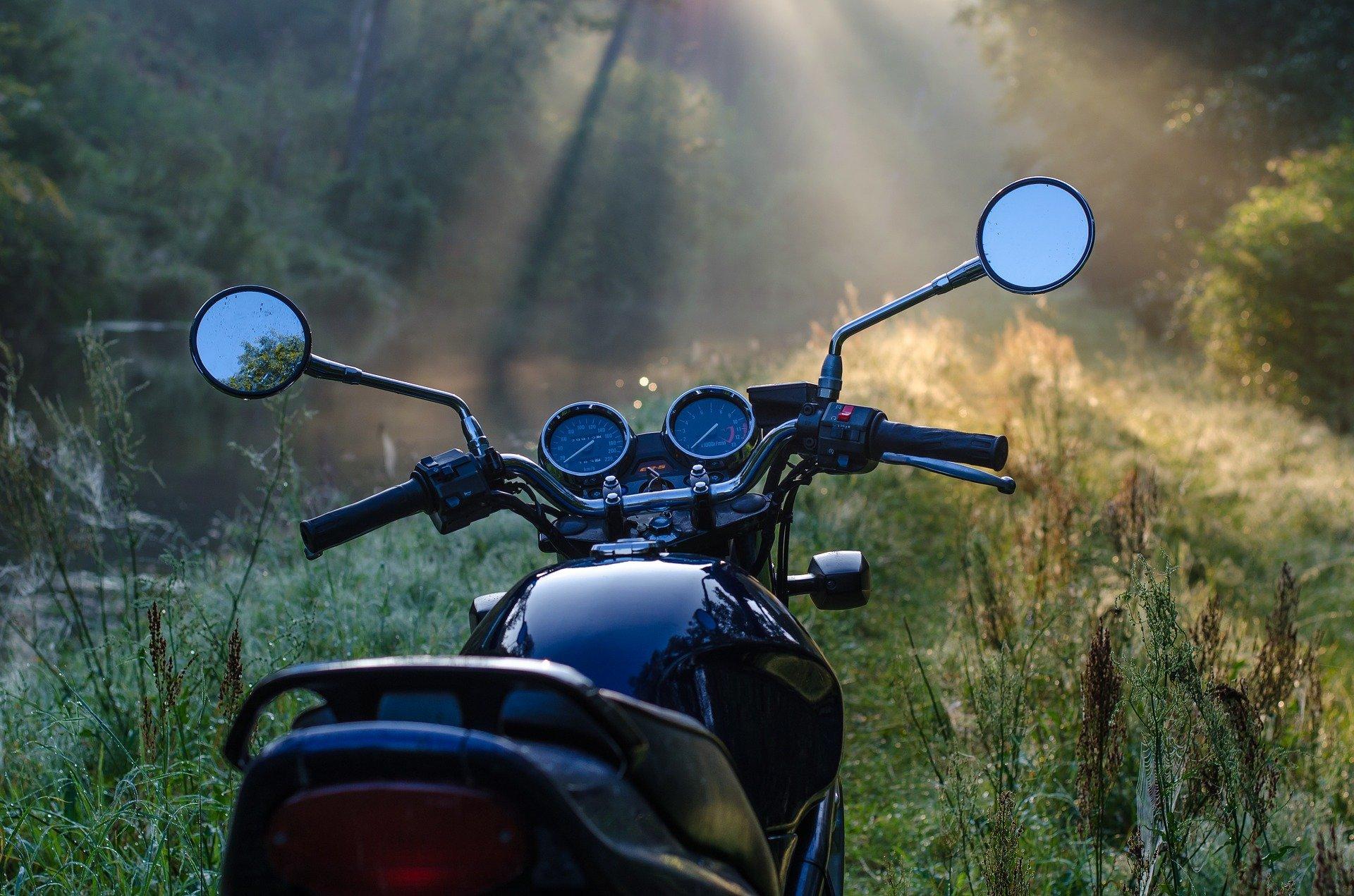Foto de uma moto preta em um campo com grama e árvores e a luz do sol vindo da parte superior esquerda. Imagem ilustrativa para texto seguro de moto.