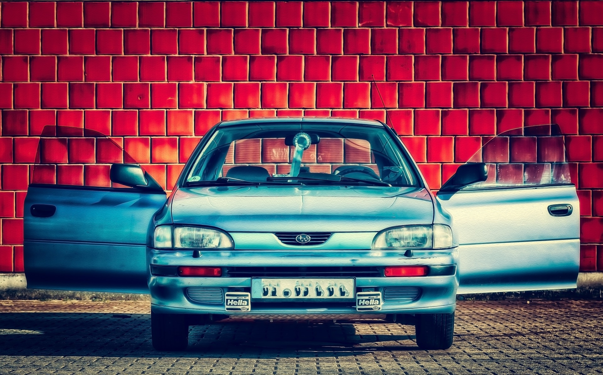 Foto de um carro azul, de frente e com as duas portas abertas, com um fundo de tijolos vermelhos. Imagem ilustrativa para texto seguro de carro usado.