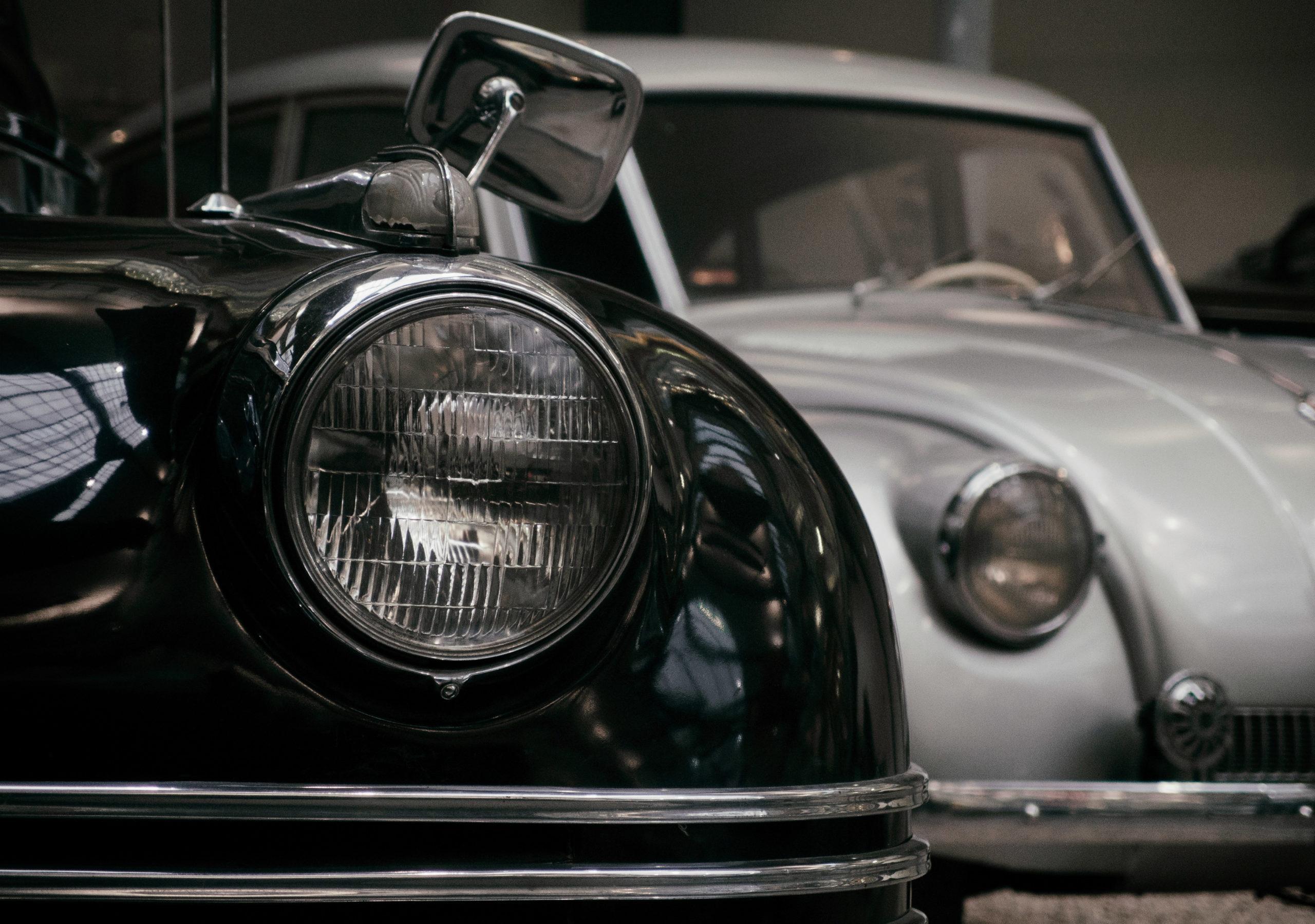 dois carros de frente, um preto e um cinza, foto focando nos faróis dos carros imagem ilustrativa seguro automotiva