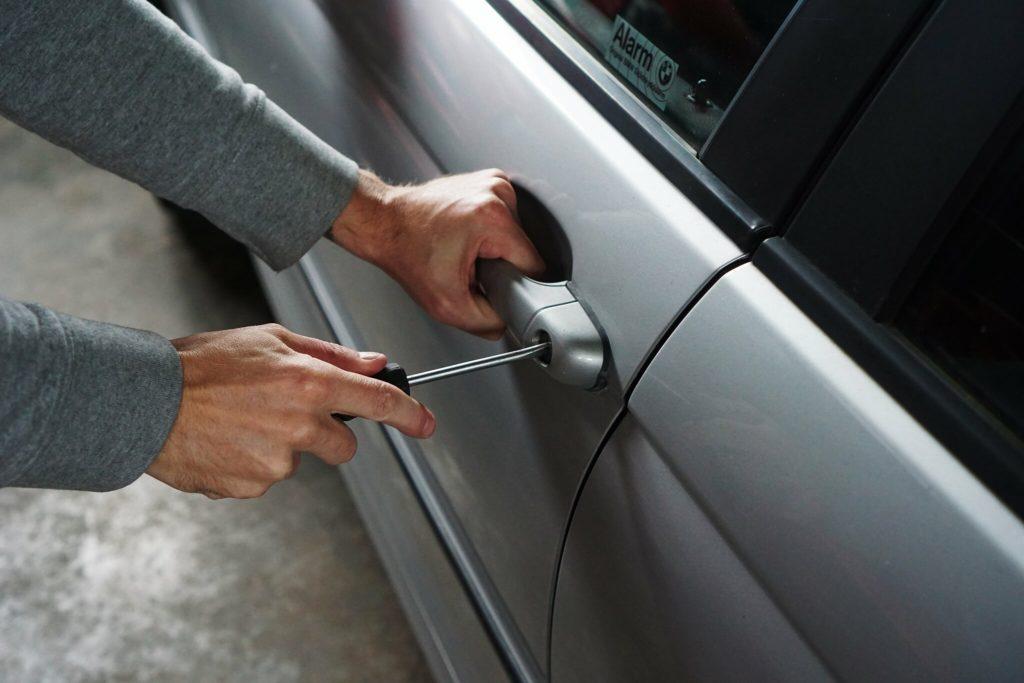 homem abrindo carro com chave de fenda imagem ilustrativa seguro automotiva
