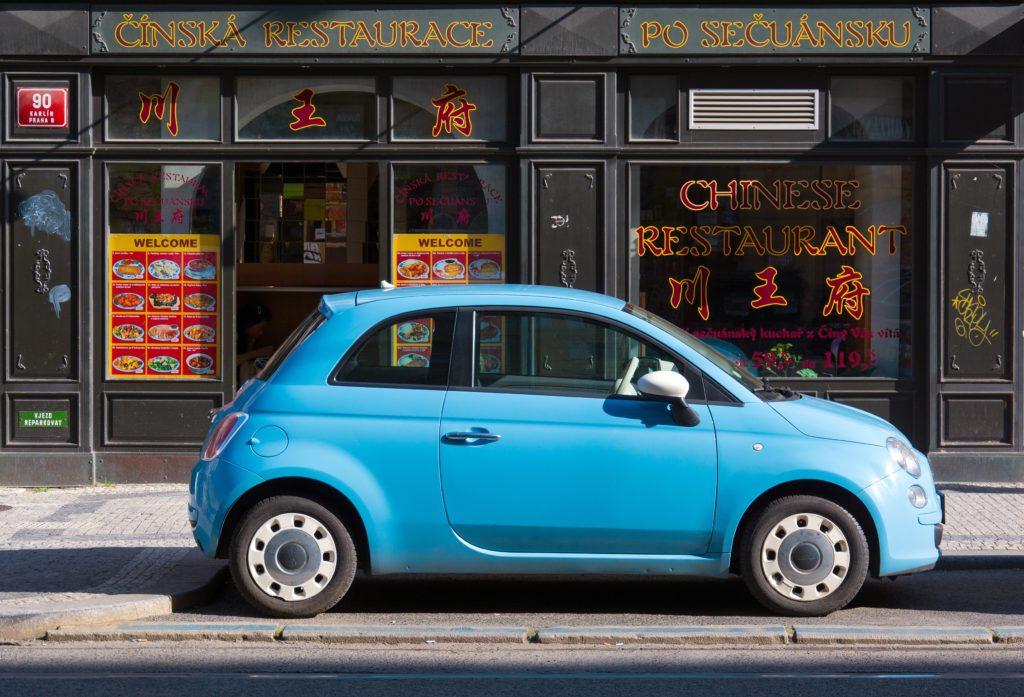 carro azul pequeno parado em frente a uma loja de comida chinesa