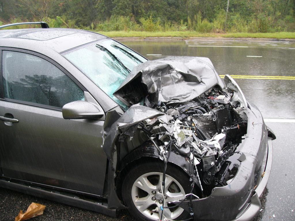 carro com a frente batido e destruída em uma estrada molhada