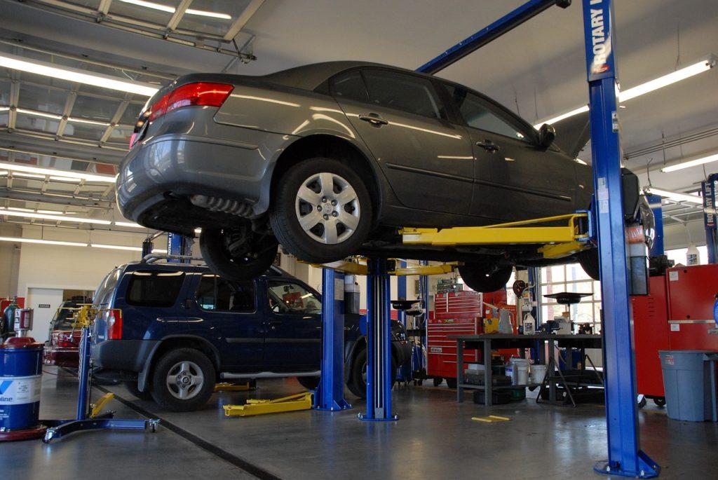 carro cinza suspenso em uma oficina mecânica