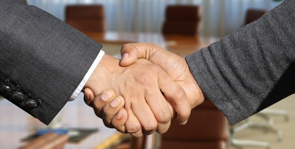 Duas mãos se apertando, vemos roupas sociais nos braços e ao fundo temos uma sala de reuniões com mesa de madeira e cadeiras marrons. Imagem ilustrativa para o texto apólice de seguro.