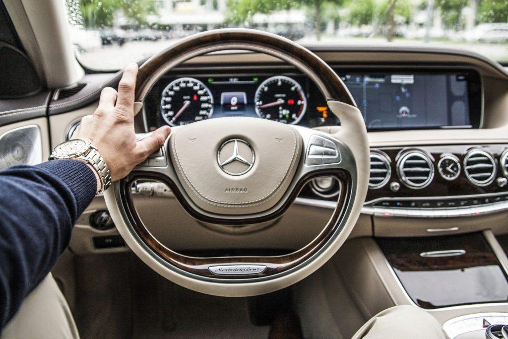 Foto de uma pessoa dirigindo um carro. Vemos o volante e o painel que possui a cor creme e na janela temos uma paisagem desfocada. Imagem ilustrativa para texto seguro de carro novo.
