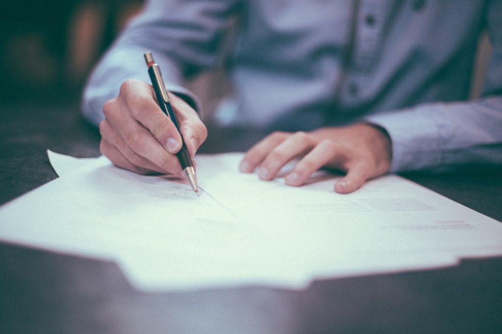 Imagem de um homem com blusa social azul, segurando uma caneta preta e dourada enquanto assina papéis em uma mesa preta. Imagem ilustrativa para o texto apólice de seguro.