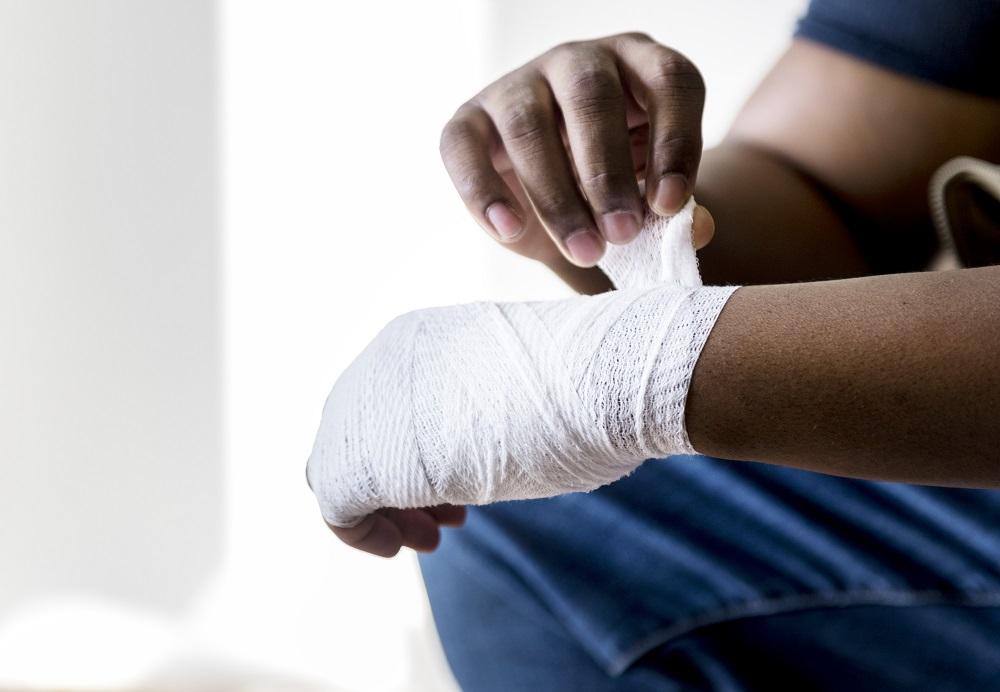 Homem de calça jeans enfaixando uma mão que está machucada. Imagem ilustrativa para texto seguros de acidentes pessoais.