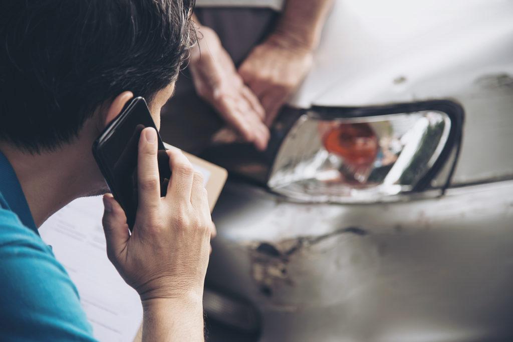 Foto de um homem com blusa azul segurando um celular preto enquanto olha para o farol direito de um carro prata que está danificado.