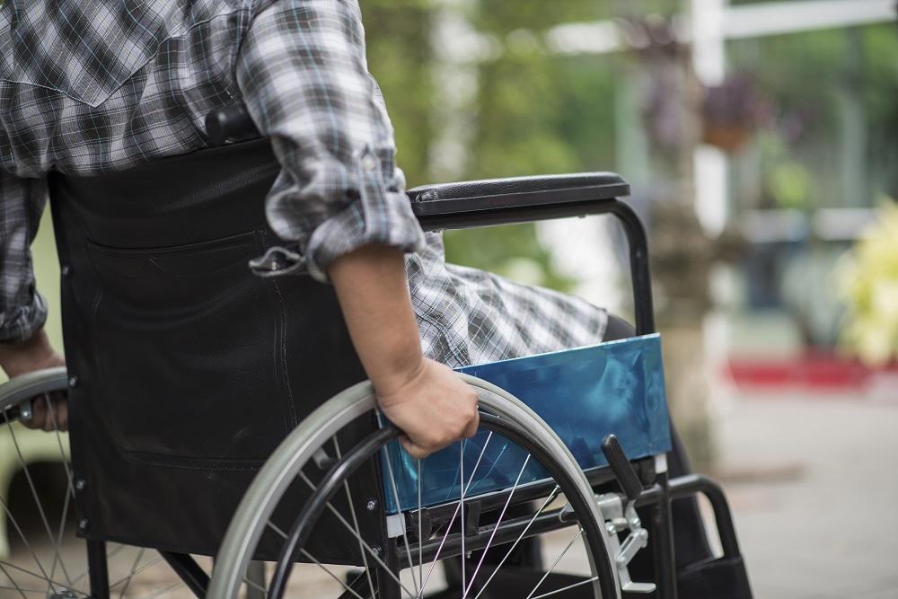 Foto de um homem de blusa xadrez verde, sentado em uma cadeira de rodas preta. Ao fundo temos um jardim desfocado. Imagem ilustrativa para texto seguros de acidentes pessoais.
