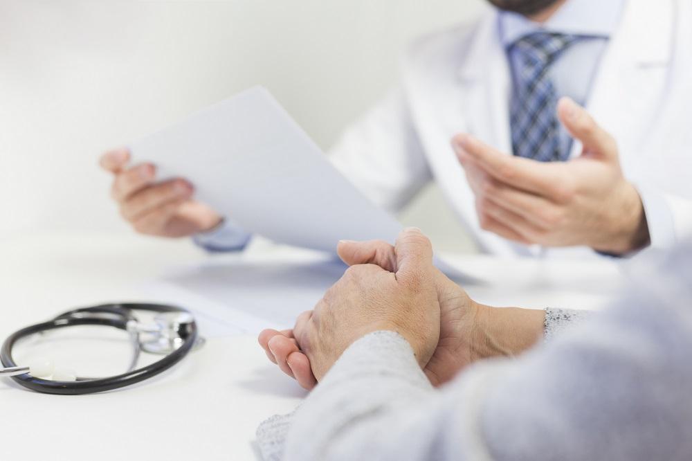 Foto da mão de uma pessoa com roupa cinza, de frente para um médico de gravata azul e jaleco. O médico segura alguns papéis e na mesa vemos um estetoscópio. Imagem ilustrativa para texto seguro de vida individual.