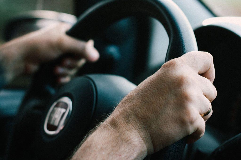 Foto de duas mãos segurando um volante, ao lado vemos um retrovisor desfocado e o painel do carro. Imagem ilustrativa para texto seguro para carro de leilão.