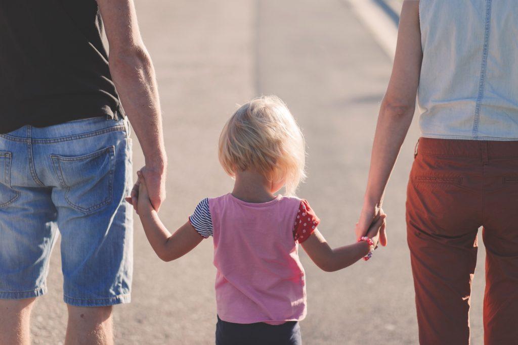 Foto de uma pessoa de blusa preta na esquerda e uma pessoa de blusa branca à direita, dando as mãos para uma menina de roupa rosa no meio. Vemos uma rua. Imagem ilustrativa para texto tipos de seguro de vida.