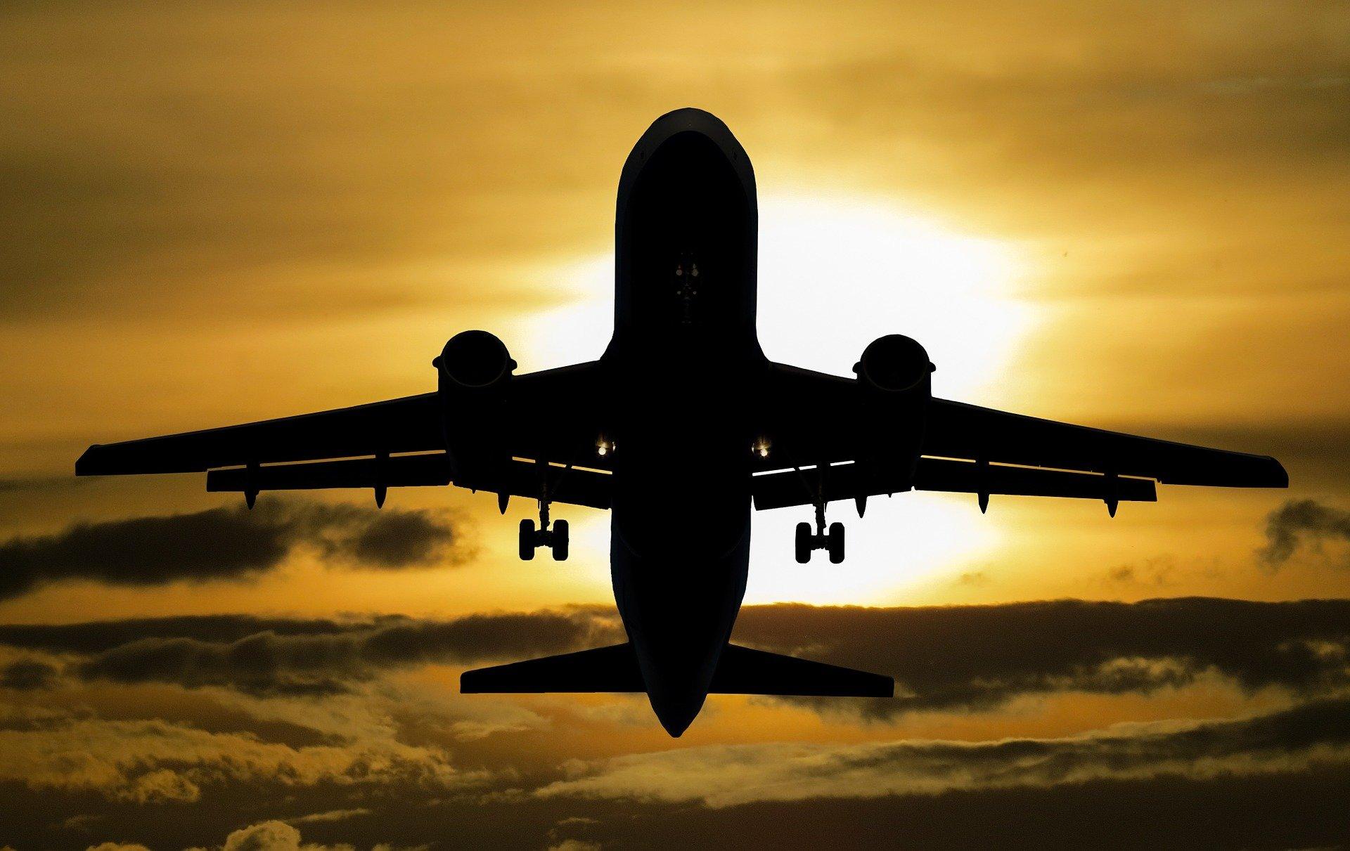 Foto de um avião contra o sol em um céu amarelado. imagem ilustrativa para texto seguro de viagem internacional.
