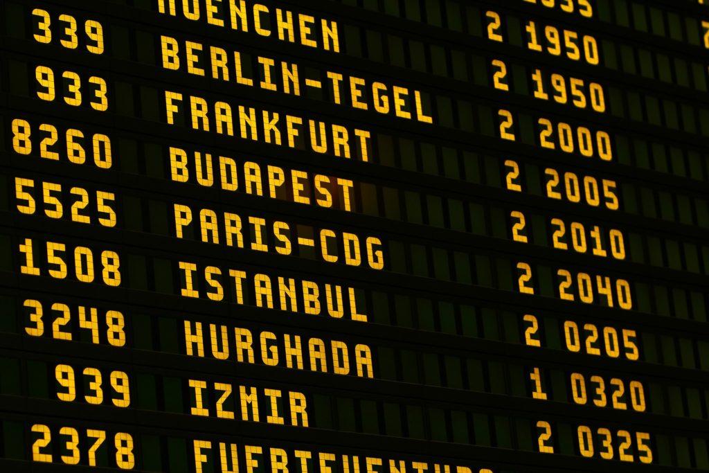 Quadro de aeroporto com os voos. O quadro é preto e todos os escritos estão em amarelo, com números nos dois lado e os destinos no meio. Imagem ilustrativa para texto seguro de viagem internacional.