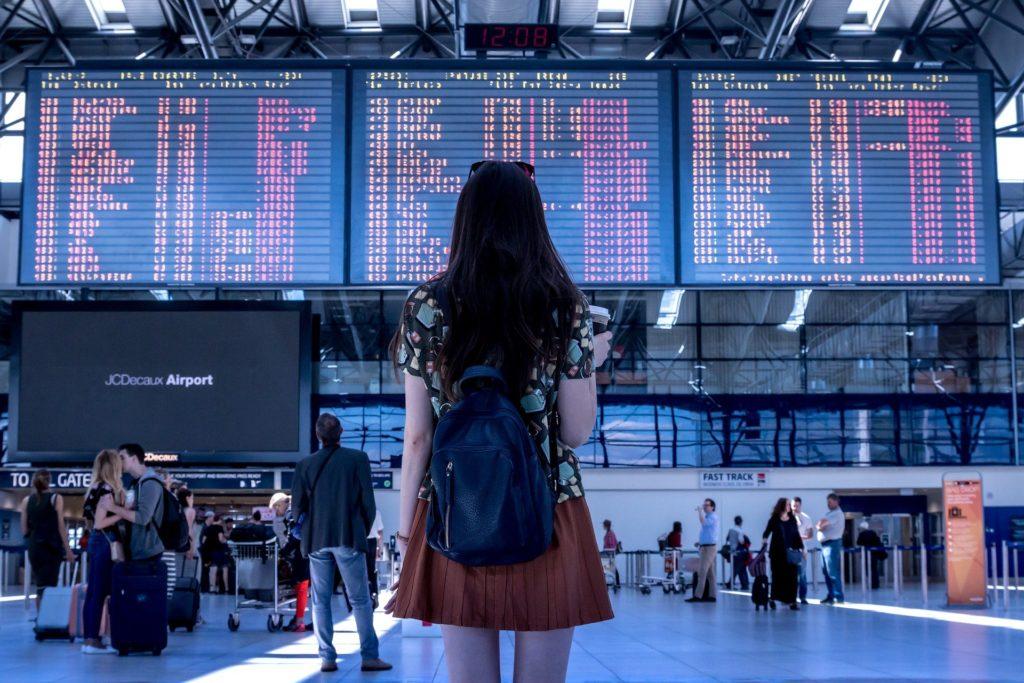 Foto de uma menina com blusa estampada, saia marrom e mochila azul, olhando o telão de voos de uma aeroporto. Ao fundo vemos outras pessoas com malas. Imagem ilustrativa para texto seguro de viagem internacional.