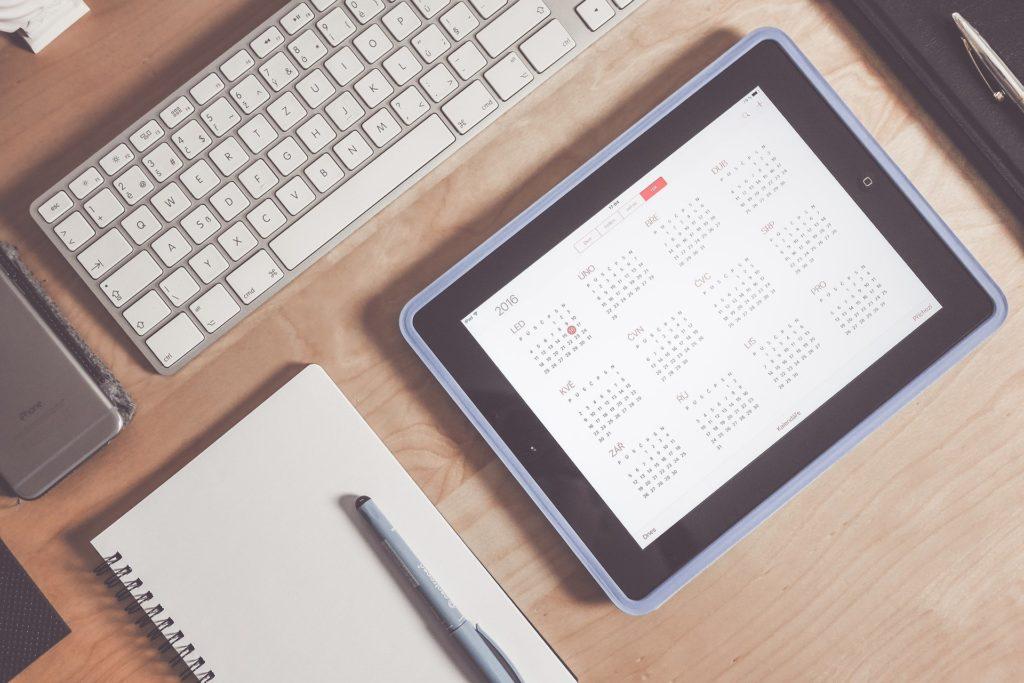 Foto de uma caderneta com uma caneta em cima, um teclado ao lado e uma tablet com um calendário.
