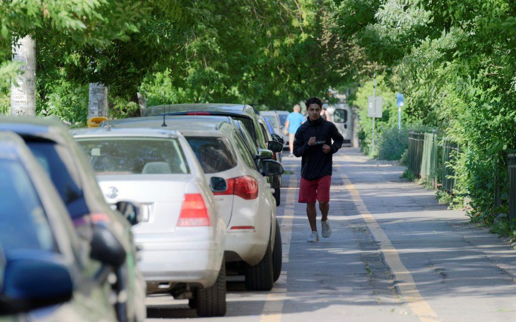 Foto com vários carros estacionados na esquerda, ao meio temos uma homem de blusa preta e short vermelho correndo. Também vemos várias árvores ao redor. Imagem ilustrativa para texto endosso de seguro.