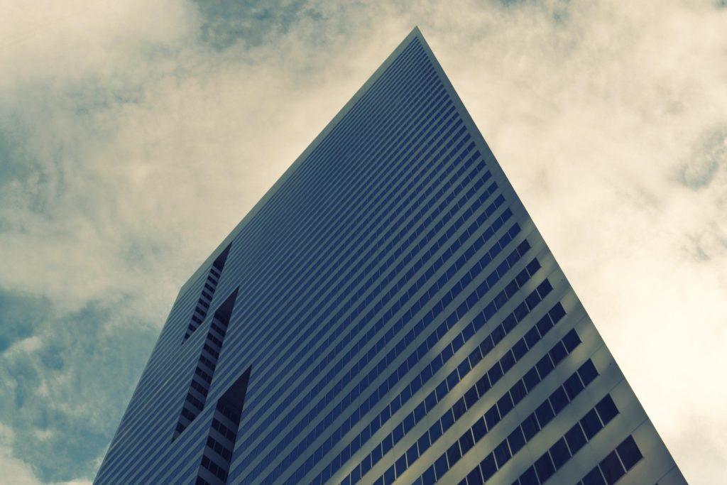 Foto de um grande prédio espelhado contra o céu azul ao fundo. Ilustração do texto seguro empresarial.