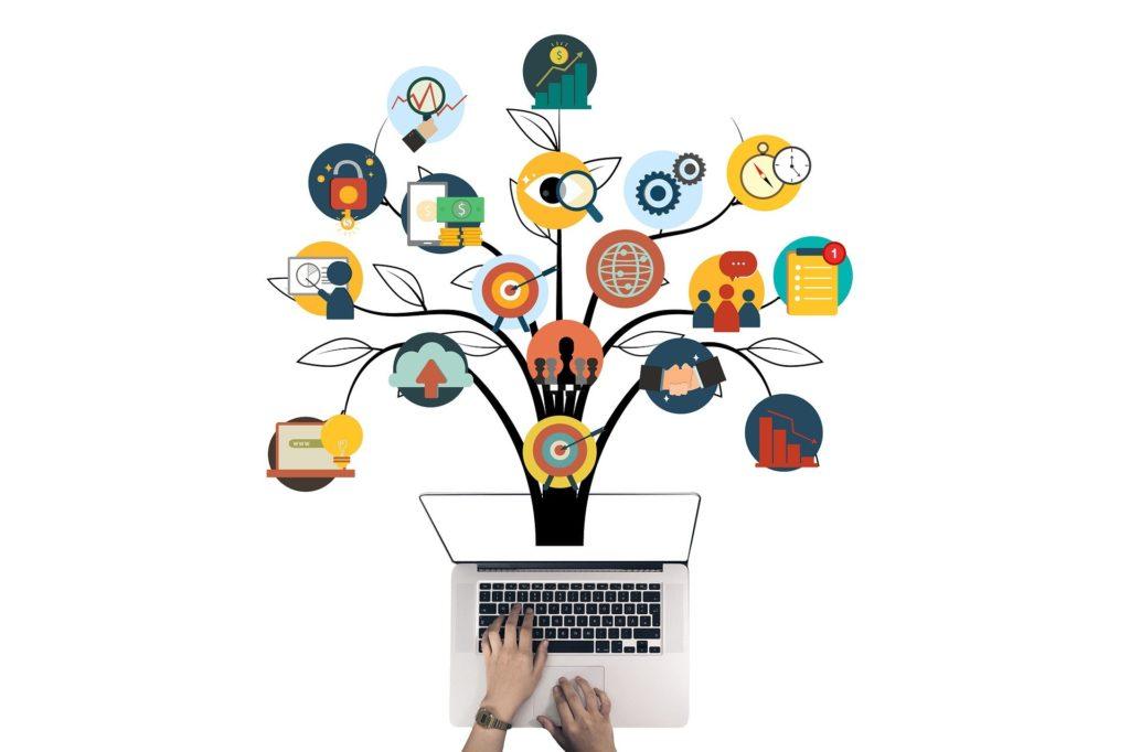 Foto de um computador cinza, em um fundo branco com duas mãos em cima. Saindo do computador temos árvores que contam com vários símbolos de conexão de uma negócio. Imagem ilustrativa para texto franquia de seguro de vida.