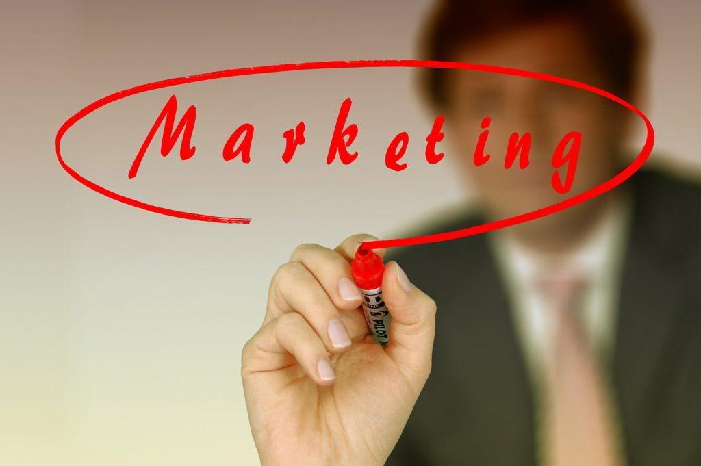 Foto de uma mão com caneta vermelha, escrevendo a palavra marketing e uma superfície. Ao fundo notamos um homem de terno. Imagem ilustrativa para texto franquia de seguro de vida.