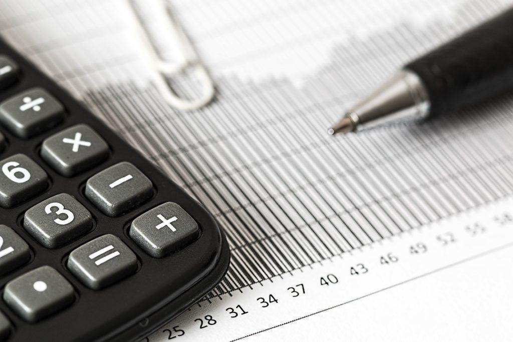 Foto de um papel com números e marcações, um clips branco, uma caneta preta e uma calculadora também preta.