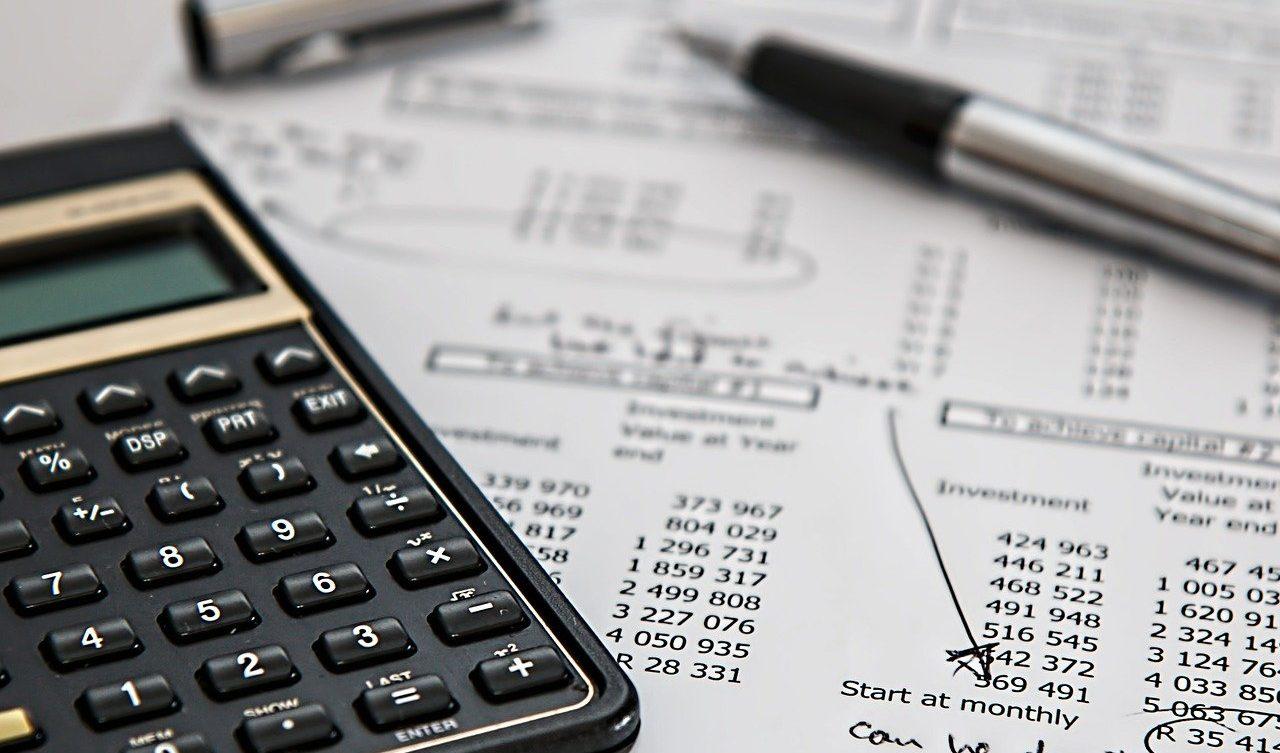 Foto de uma calculadora preta, papel com números atrás e uma caneta prata ao lado. Imagem ilustrativa para texto seguro de viagem internacional.