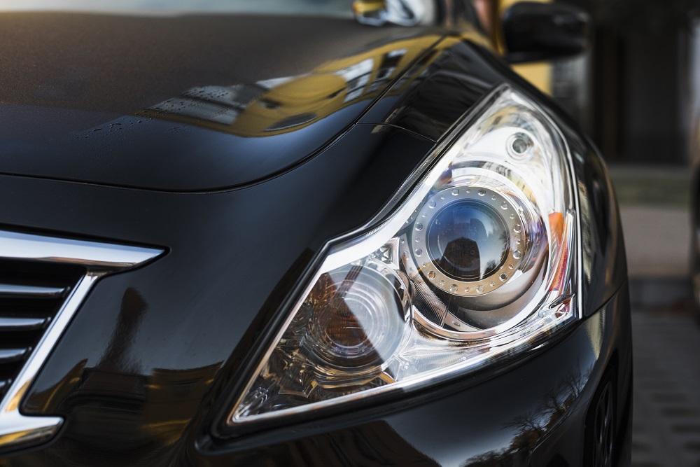 Foto do farol direito de um carro preto. Imagem ilustrativa para texto seguro para carro blindado.