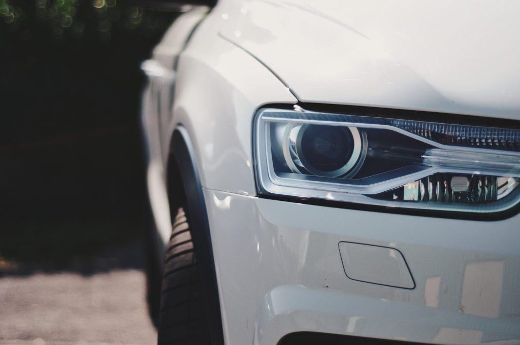 Foto da lanterna de um carro branco, ao lado vemos parte de um asfalto. Ilustração para o texto seguro de frota.